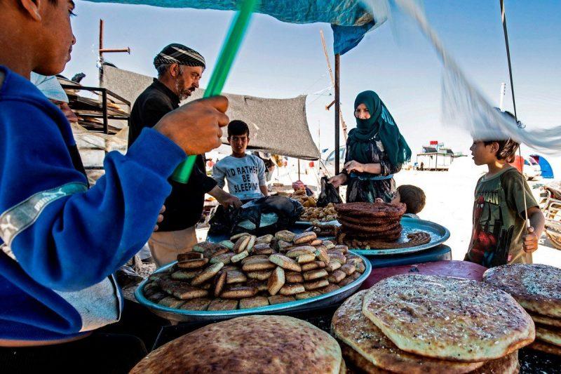 Warga yang sedang menanti makanan di sebuah kamp pengungsi di Suriah pada 10 Mei 2020 [DELIL SOULEIMAN / AFP / Getty Images]