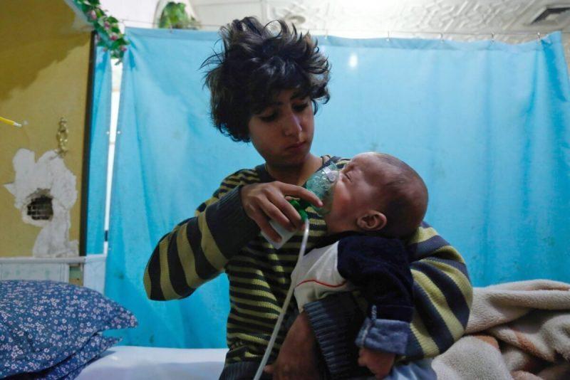 Seorang bocah Suriah memegang masker oksigen di wajah seorang bayi di sebuah rumah sakit darurat, pascaserangan gas yang dilaporkan di daerah Douma, wilayah Ghouta timur, di Damaskus pada 22 Januari 2018. [HASAN MOHAMED / AFP via Getty Images]