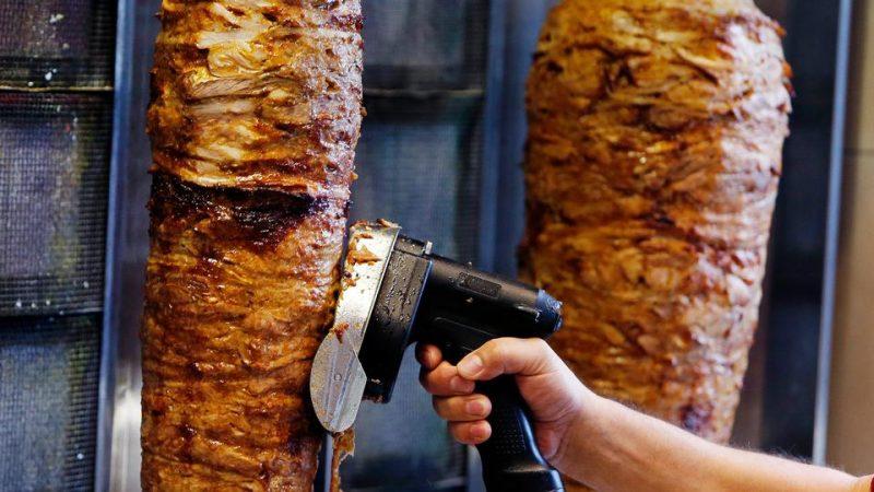 Seorang pria mengiris daging dari rotisserie doner spit di dalam sebuah restoran doner di Frankfurt, Jerman, Kamis, 30 November 2017. (AP)