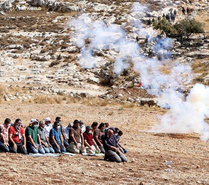 Pengunjuk rasa Palestina melaksanakan shalat di tengah asap gas air mata ketika serdadu zionis 'Israel' membubarkan unjuk rasa menentang perluasan permukiman ilegal di dekat Desa Beit Dajan, timur Nablus. (Jaafar Ashtiyeh/AFP)