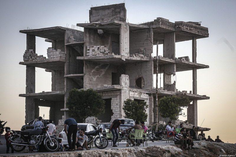 Warga Suriah melanjutkan kehidupan mereka di antara bangunan-bangunan yang rusak akibat peperangan di Idlib, Suriah, pada 14 Agustus 2020 [Muhammed Said / Anadolu Agency]