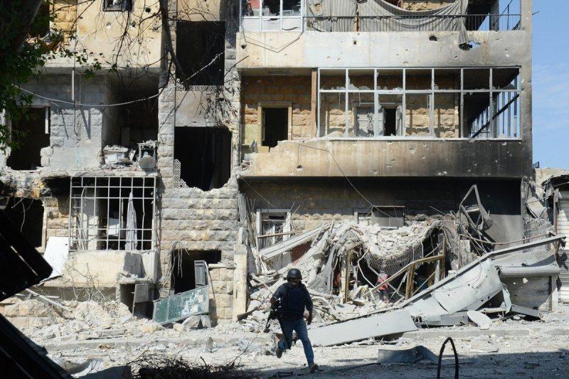 Seorang juru kamera TV berlari melintasi jalan di antara reruntuhan bangunan untuk mencari perlindungan di Aleppo, Suriah pada tanggal 5 Oktober 2012 [TAUSEEF MUSTAFA / AFP / Getty Images]