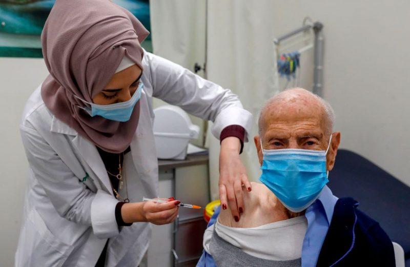 Seorang petugas kesehatan memberikan vaksin Covid-19 kepada seorang pria lanjut usia Palestina di Layanan Kesehatan Clalit di Baitul Maqdis timur, pada 7 Januari 2021 [AHMAD GHARABLI / AFP via Getty Images]