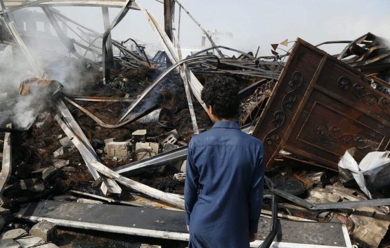 Seorang anak laki-laki memandang puing-puing bangunan setelah serangan udara yang dilakukan koalisi yang dipimpin Arab Saudi pada 2 Juli 2020 di Sana'a, Yaman. Foto: Mohammed Hamoud/Getty Images
